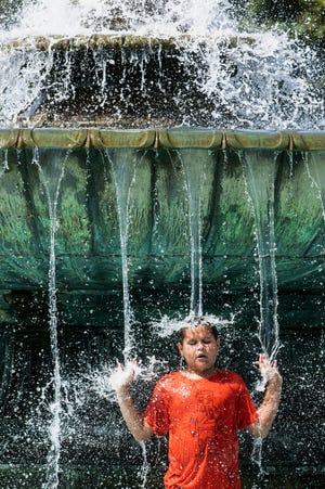 Alex Paladino cools off at the Eakins Oval fountain in Philadelphia on Sunday, July 21, 2019. The East Coast on Sunday sweated through another day of heat and humidity in a stretch of weather so oppressive that organizers in Boston cancelled a road race, Delaware Civil War re-enactors got the day off and the New York Police Department implored residents to take it easy.