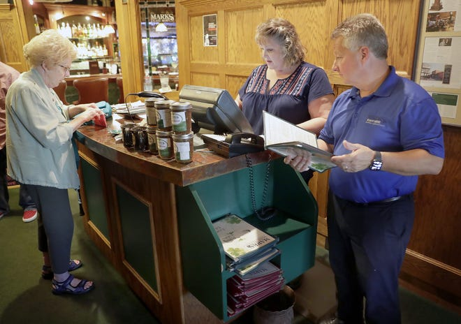 Calm before the storm: Mark's East Side was conducting business as usual Friday, but has been closed since then when a storm cut off its electricity Saturday. Shown here are Mark Dougherty, right, and Rhoda Steffel, front house manager, helping customer Fran Bollenbeck, left.