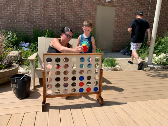 Brycen Welsh, 6, of Browns Mills plays a game with mom, Dusty Welsh, at Brick Plaza's new boardwalk area.