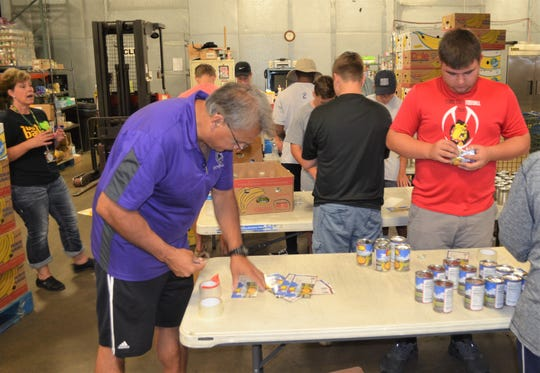 Lakeview head football coach Jerry Diorio and members of the Spartans volunteer at the Food Bank of South Central Michigan.