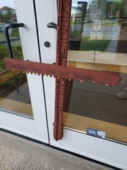 """An edited image provided by Battle Creek Pride shows a  decorated cross that was allegedly zip-tied to First Congregational Church with the words repent as well as a """"vulgar, transphobic message"""" on Sunday. The church is the site of the organization's candlelight vigil honoring the lives lost in the United States in the past year of those who identify as trans."""