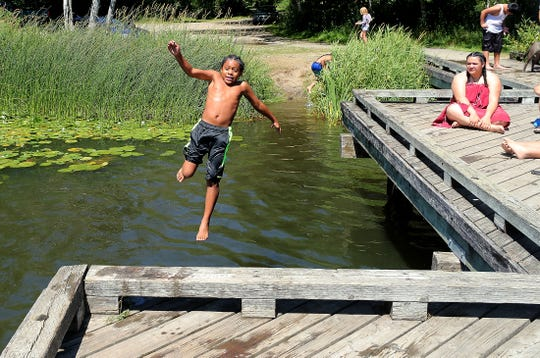 Kaisaiah Wilson, 11, cools off with a jump off the dock at Long Lake County Park in Port Orchard in July.