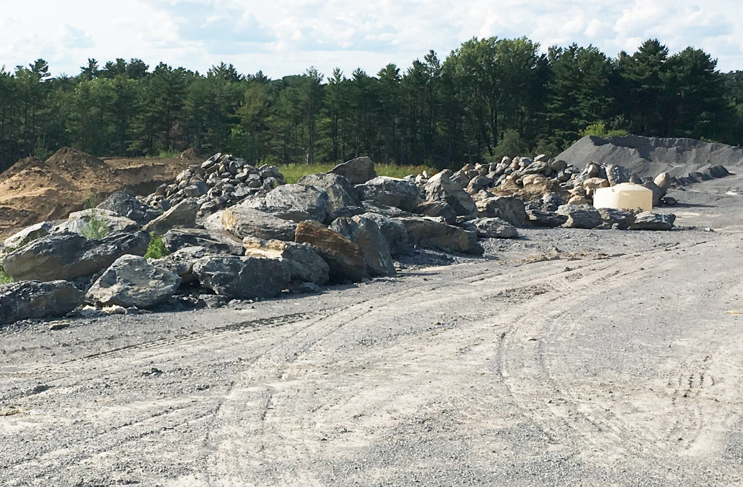 Boulders, gravel and topsoil are stockpiled at the edge of a housing development under construction at the O'Brien Farm in South Burlington on July 14, 2019.