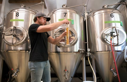 Head brewer Dominic Jacob measures the gravity of a Farmhouse Ale at Cold Spring Brewery located in Lower Township, NJ.