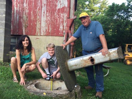 Mercer Elementary School teacher Erinn Cox, Farm Manager Ben Gressle, and Daryl Meyerrenke checking the water level in the cistern.