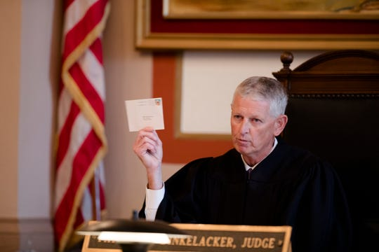 Judge Patrick T. Dinkelacker reads cards he said her received at his home during an execution of sentence of Former judge Tracie Hunter on Monday, July 22, 2019 in Cincinnati. Hunter was ordered to serve a six-month jail sentence that was imposed more than four years ago.