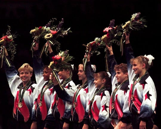 July 23, 1996: Members of the U.S. women's gymnastics team wave to the crowd after being awarded their gold medals in the team competition at the centennial Summer Olympic Games in Atlanta. From left: Amanda Borden, Dominique Dawes, Amy Chow, Jaycie Phelps, Dominique Moceanu, Kerri Strug, and Shannon Miller.