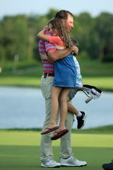 Jim Herman hugs his children, Abigail and Andrew, on the 18th green after winning the Barbasol Championship at Keene Trace Golf Club on July 21, 2019 in Nicholasville, Kentucky.