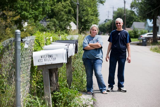 Jamie Twehues, left, and Byron Lile,  community advocates, stand along Club House Drive in the Latonia Lakes community. Residents who live off Club House Drive are forced to use these mailboxes and others. The Covington postmaster claims the roads are not safe for mail delivery even after the county and residents' $2 million investment in new roads.  The roads were finished in September 2017, which smoothed them out and added turnaround areas on the side streets. The setup causes problems for elderly residents, frequent mail mix-ups and stolen packages.