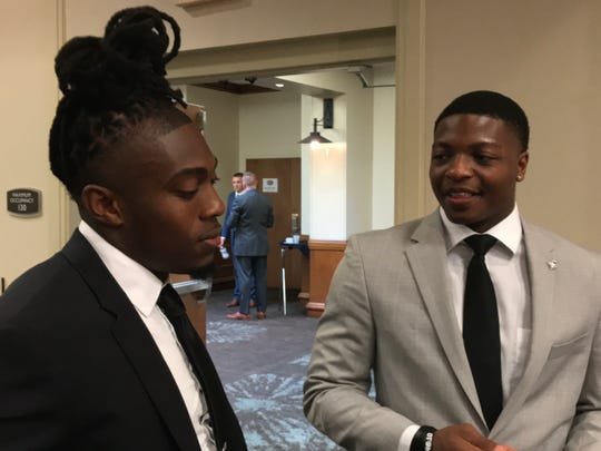 Austin Peay senior running back Kentel Williams (right) talks with senior teammate Juantarius Bryant during OVC Media Day on Monday in Nashville.