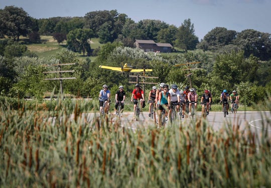 A crop dusting plane takes off as cyclists roll into Anita during RAGBRAI on July 22, 2019.