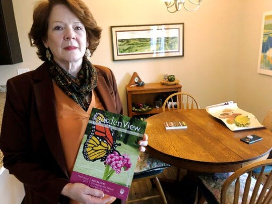 In this July 12, 2019, photo, former Iowa State University administrator Teresa McLaughlin poses at her Coralville, Iowa, home with a magazine featuring Nature Connects, the outdoor sculptures made of Lego bricks that she managed. The university has withdrawn allegations of wrongdoing against McLaughlin and paid her $225,000 to settle a legal dispute that derailed the popular art program.