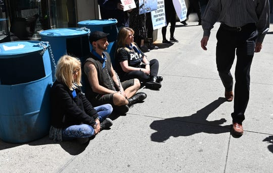People walk past PETA supporters outside the Millennium Times Square New York in midtown Manhattan April 23, 2019, chained to plastic barrels similar to ones that dogs trained for the Iditarod race in Alaska used for protection from wind chills as low as minus 19. - Millennium Hotels and Resorts, whose hotel in Alaska sponsors the Iditarod, is poised to face protesters on the heels of PETA's first-ever expose of dog-sledding operations owned by two Iditarod champions.