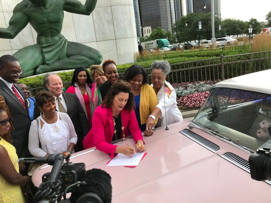 Using the hood of a 1958 pink Cadillac as a desk,  Gov. Gretchen Whitmer  signs the bill that designates part of the Lodge Freeway in Detroit as the Aretha L. Franklin Memorial Highway.
