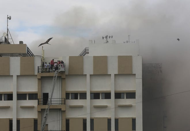 People are rescued from a nine-story building with offices of a state-run telephone company during a fire in Mumbai, India, Monday, July 22, 2019.