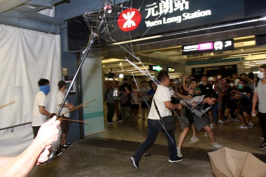 In this Sunday, July 21, 2019, photo, thugs in white shirts armed with metal rods and wooden poles attack commuters at a subway station in New Territory in Hong Kong.