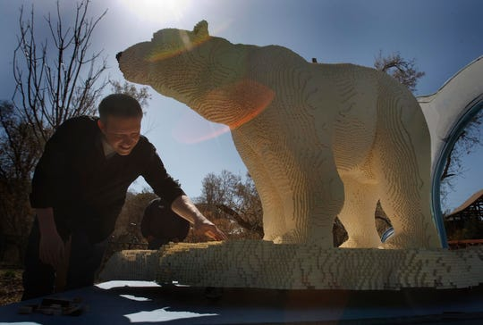 In this April, 24, 2013 file photo, Lego artist Sean Kenney shows off a sculpture of a polar bear at the Hogle Zoo in Salt Lake City.