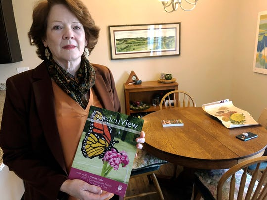 In this July 12, 2019 photo, former Iowa State University administrator Teresa McLaughlin poses at her Coralville, Iowa home with a magazine featuring Nature Connects, the outdoor sculptures made of Lego bricks that she managed.