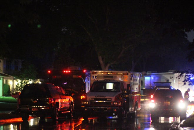 Emergency vehicles line up outside a home where a barricaded gunman is holed up after shooting her husband.
