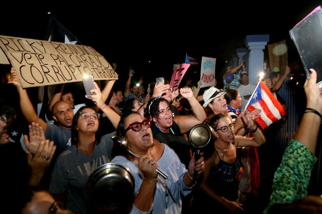 Protesters gather outside the Yolanda Guerrero Cultural Center in Guaynabo, Puerto Rico, after Gov. Ricardo Rossello left a meeting with mayors from his party Sunday, July 21, 2019. Rossello said Sunday evening that he will not resign but he will not seek re-election.