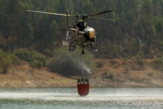 A helicopter takes water at the Vergancinho dam to extinguish a wildfire near Colos village, in central Portugal on Monday, July 22, 2019.