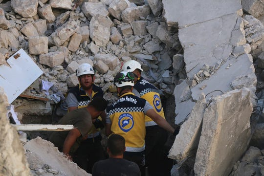 This photo provided by the Syrian Civil Defense White Helmets, which has been authenticated based on its contents and other AP reporting, shows Syrian White Helmet civil defense workers search for victims from under the rubble of a destroyed building that hit by Syrian government and Russian airstrikes, in the northern town of Maaret al-Numan, in Idlib province, Syria, Monday, July 22, 2019.