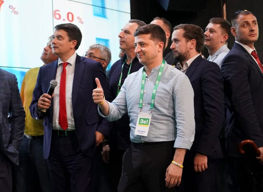 Ukrainian President Volodymyr Zelenskiy, center, reacts with his team as they look at the election results at his party's headquarters after a parliamentary election in Kiev, Ukraine.