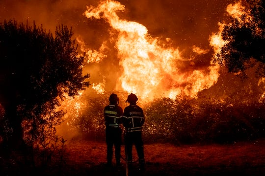 Fighters try to extinguish a wildfire near Cardigos village, in central Portugal on Sunday, July 21, 2019.