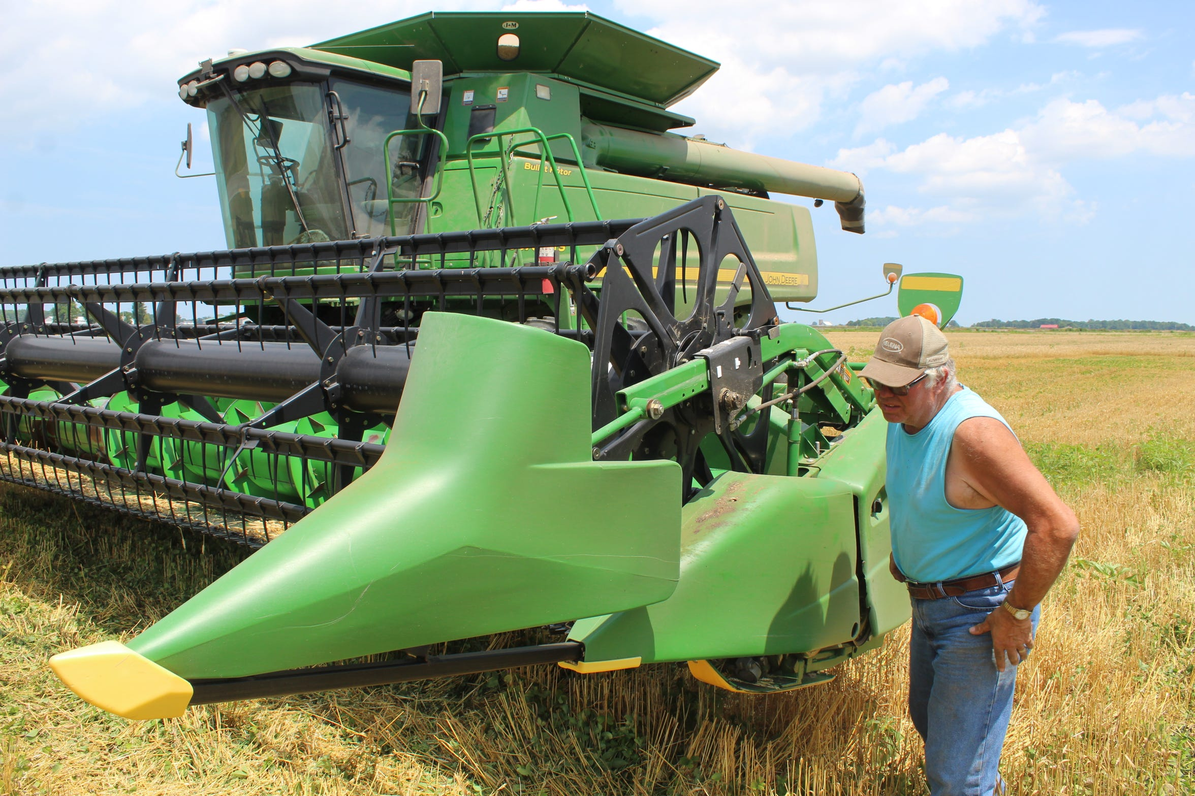 Farmer Ron Laubacher looks over his combine in a wheat field near Benton Carroll Road in Ottawa County.