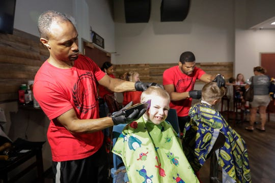 Lucas Cubito, 6, gets his haircut at the Daniels Back to School Bash at Spring Lake Church in downtown Green Bay on Monday. Imago Dei The Barber Lounge offered free haircuts, styles and braids for kids.