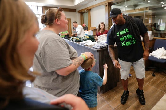 Mike Daniels greets families Monday during his Daniels Back to School Bash at Spring Lake Church. On Wednesday, the Packers released the defensive lineman.