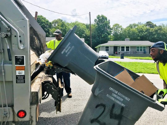 Leroy Terry, left, and Kwanshawn Fuller with the Greater Greenville Sanitation District pick up household garbage Monday, July 22, 2019, in a neighborhood off White Horse Road.