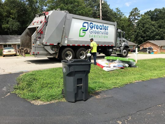 Leroy Terry with the Greater Greenville Sanitation District tosses garbage piled up by the road in a neighborhood off White Horse Road on Monday, July 22, 2019.
