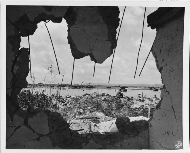 View of part of the Southern Assault Beach, from a ruined building in  July 1944. The Orote Peninsula is in the distance. Note machine gun crew in right center.