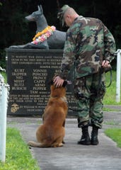 Navy Petty Officer 2nd Class Blake Soller, a military working dog handler, pets the head of working dog Rico, at the War Dog Cemetery, on Oct. 27, 2006, located on Naval Base Guam.