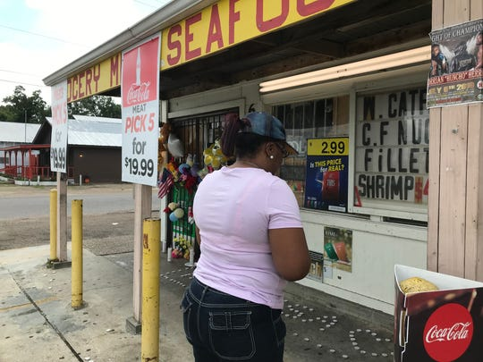 Bridgette Ferguson prays at Steelman Grocery on Monday, July 22, 2019, where 59-year-old Lisa Nguyen was shot to death during an armed robbery Saturday, July 20, 2019.