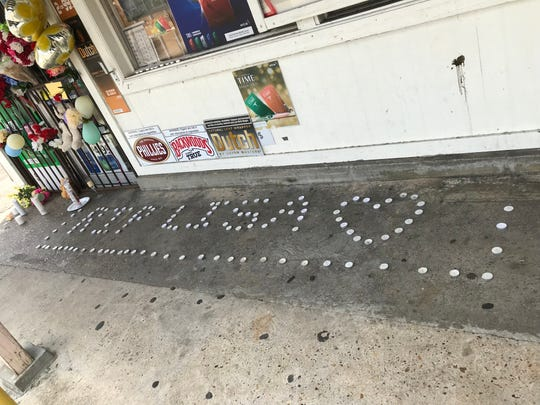 """Tealight candles that spell out """"RIP Lisa"""" with a heart line the entrance to Steelman Grocery, where 59-year-old Lisa Nguyen was killed during an armed robbery Saturday, July 20, 2019."""