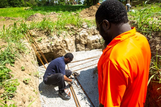 Sohaib Orsod, left, secures a piece of rebar while helping build a foundation for a shed with Ousaimou Keita, president of the Executive Committee at the Iowa City Mosque, Monday, July 22, 2019, at the Al-Iman Cemetery in Iowa City, Iowa.