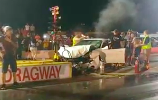 People surround a wrecked vehicle at the Jackson Dragway on July 20, 2019, in Jackson, Tenn. Jerry Oliver allegedly drove his vehicle the wrong way down the dragstrip after jumping a ditch, narrowly missing two teams prepared to start their race when he crashed into the light tree near the start line.