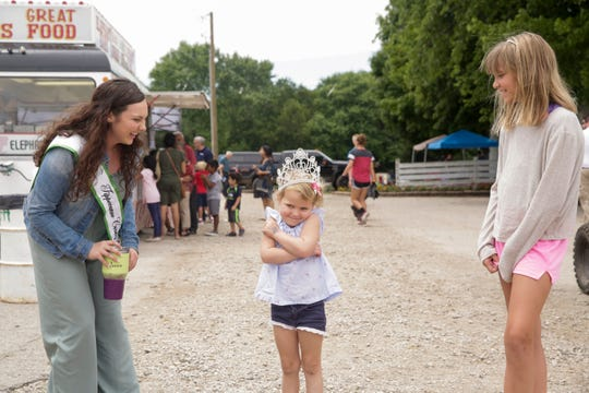 Miss Tippecanoe County 4-H Queen Magdalene Pearl, left, reacts after placing her crown on Chloe Fish, 4, as her cousin, Grace Karns, 10, smiles at right, during the third day of the 2019 Tippecanoe County Fair, Monday, July 22, 2019 in Lafayette.The fair continues until Saturday, July 27.