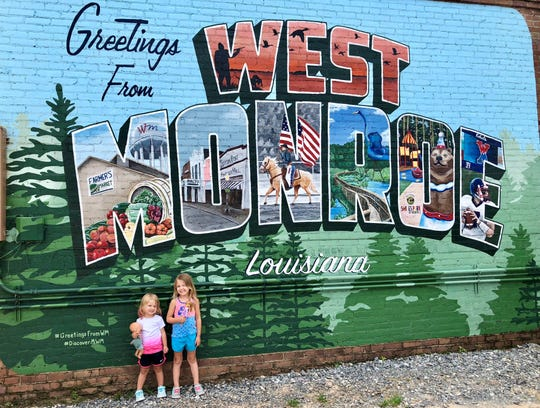 Marie and Avery Guidry stand in front of a mural in downtown West Monroe, which they visited with their parents while on a road trip along U.S. Highway 80.