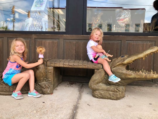 Avery and Marie Guidry play with their dolls on an alligator bench in downtown West Monroe. Reporter Leigh Guidry and family are exploring the state by taking the back roads along Louisiana Byways. This road trip took them along U.S. Highway 80.
