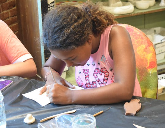 Destiny Aichaw One, 11, works on creating more detailed pieces for her clay owl during the Major Arts for Minors event at Art and Clay on Main. Part of the Lancaster Festival, these events let kids experience different type of creative venues.