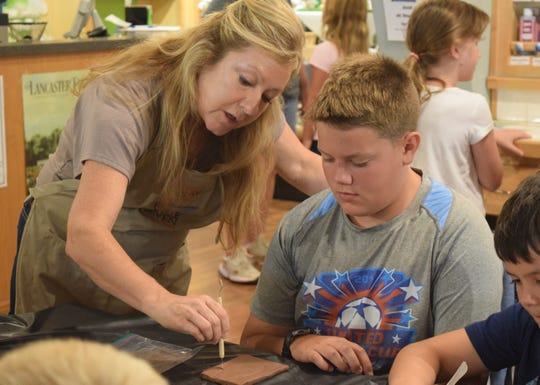 Kelly Jones demonstrates outlining a shape in clay during the Major Arts for Minors event at Art and Clay on Main Monday. Part of the Lancaster Festival, these events let kids experience different type of creative venues.