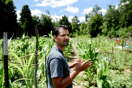 Dilli Chapagai, immigrant and refugee liaison for the Greater Lansing Food Bank Garden Project, visits the Webster Farm Community Garden weekly. The garden supports about 80 immigrant and refugee families.