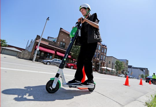 Steven Johnson of Milwaukee takes a ride on a Lime scooter outside Boo Boo's Sandwiches and Soup Brothers onSouth 2nd Street in Milwaukee.