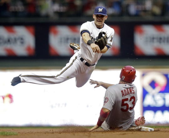 St. Louis Cardinals' Matt Adams breaks up a double play as Milwaukee Brewers' Scooter Gennett makes a late throw to first on a ball hit by David Freese during the second inning of a baseball game Tuesday, Aug. 20, 2013.