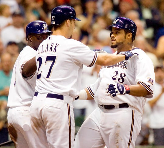 Prince Fielder is congratulated by Brady Clark and Bill Hall after hitting a monster three run homer in the 7th inning against the Colorado Rockies Thursday August 24, 2006.