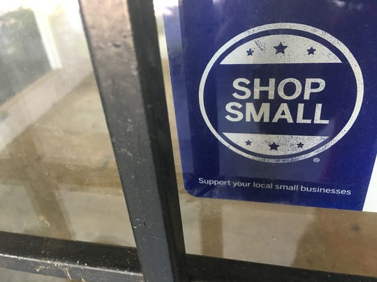 "A ""shop small"" sticker stands on the front window of the former Stern Brothers store in Montgomery."