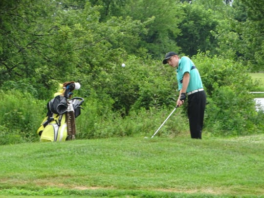 Newark Catholic's Garrett McCarthy pitches onto the 18th green on Monday at Clover Valley Golf Club during the final day of the Licking County Junior Golf Association tour.